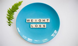"""Image of a blue plate on a white background. Off-white tiles on the plate spell """"weight loss."""""""